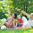 Happy young couple with their children have fun at park — Stock Photo #6835279