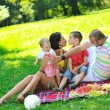 Happy young couple with their children have fun at park — Stock Photo #6835774