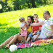 Happy young couple with their children have fun at park — Stock Photo #6836931