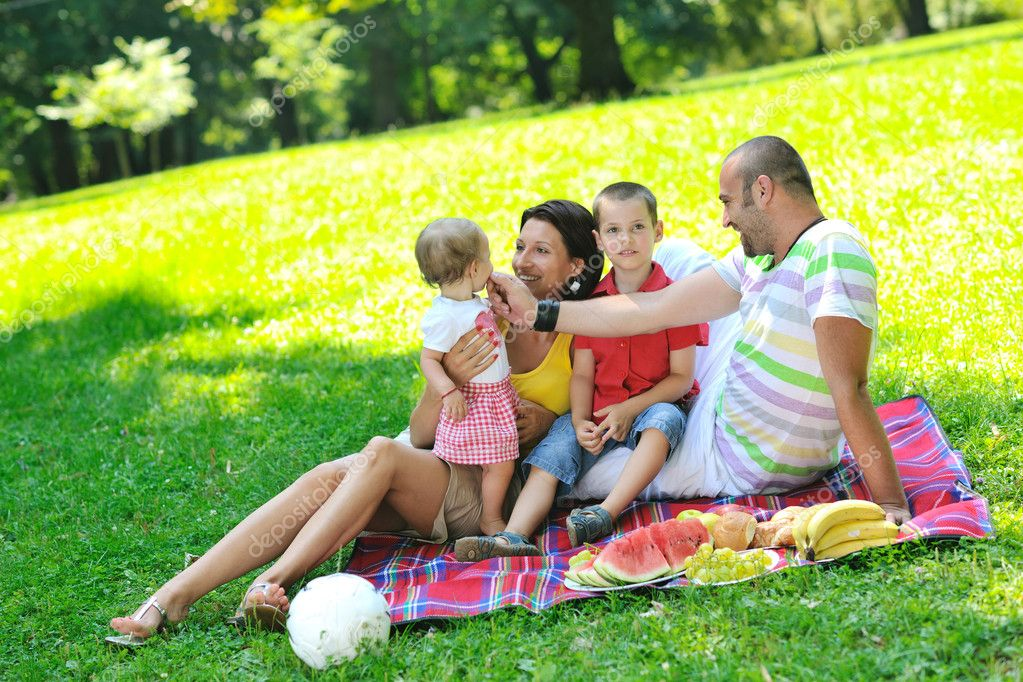 Happy young couple with their children have fun at beautiful park outdoor in nature — Stock Photo #6836931