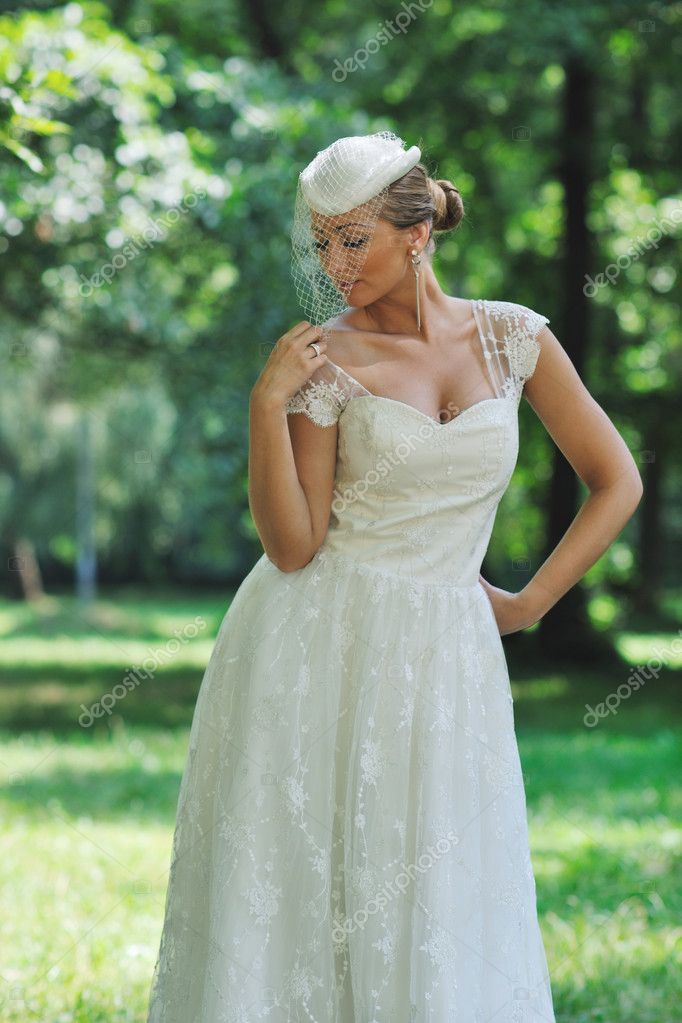 Beautiful bride woman in fashion wedding dress posing outdoor in bright park at morning — Stock Photo #6850314