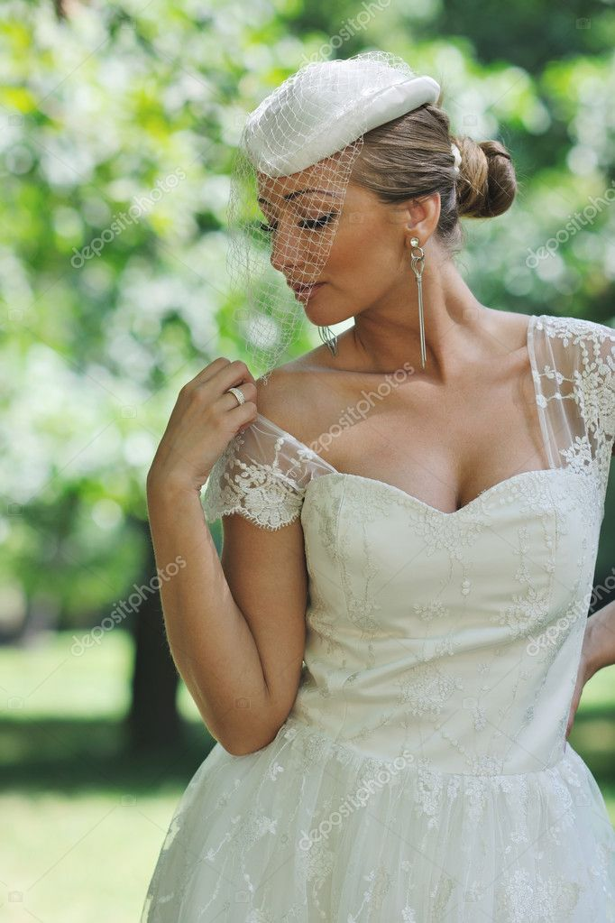 Beautiful bride woman in fashion wedding dress posing outdoor in bright park at morning — Stock Photo #6850429