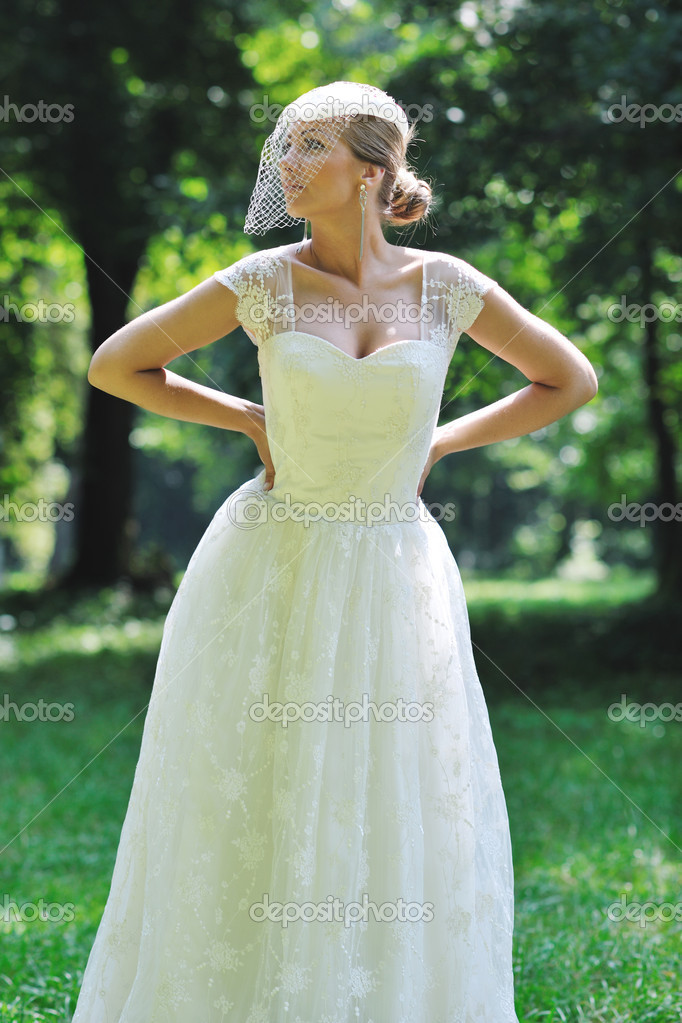 Beautiful bride woman in fashion wedding dress posing outdoor in bright park at morning — Zdjęcie stockowe #6850722