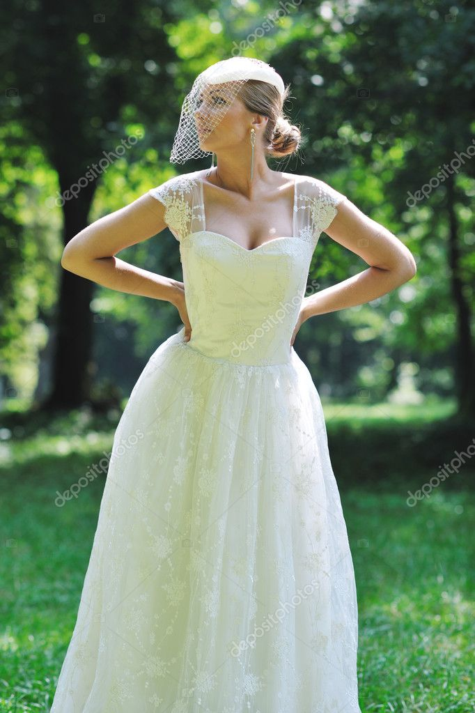 Beautiful bride woman in fashion wedding dress posing outdoor in bright park at morning — Stockfoto #6850722