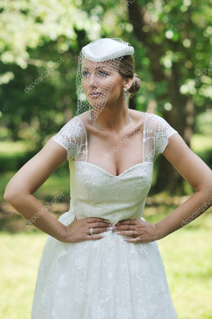 Beautiful bride woman in fashion wedding dress posing outdoor in bright park at morning — Stock Photo #6850772