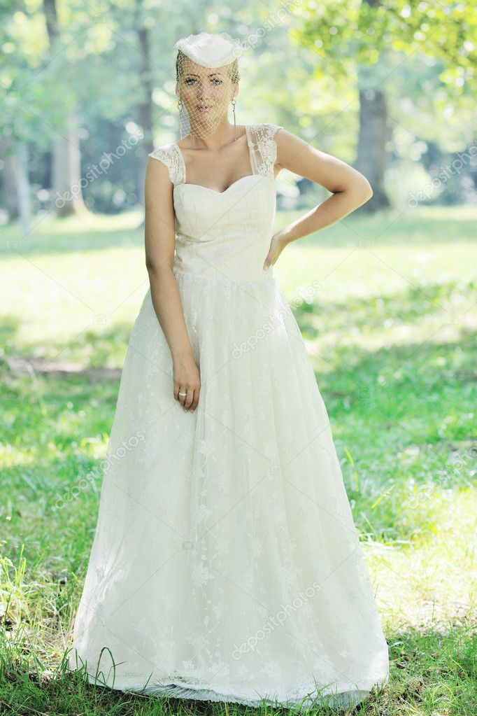 Beautiful bride woman in fashion wedding dress posing outdoor in bright park at morning — Stock Photo #6851101