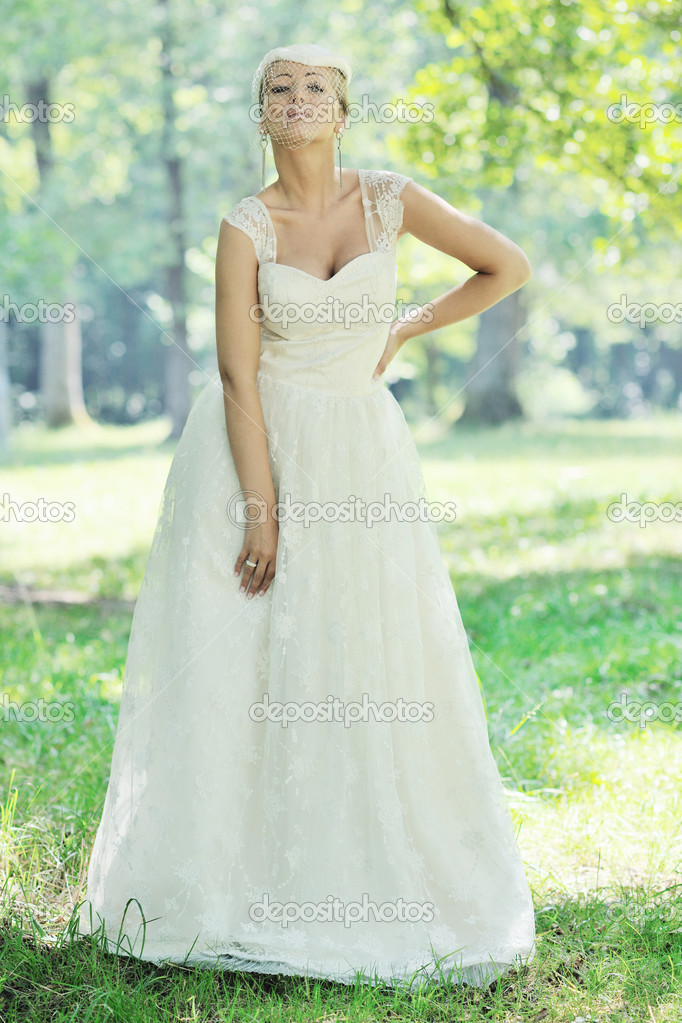 Beautiful bride woman in fashion wedding dress posing outdoor in bright park at morning — Stock Photo #6851148