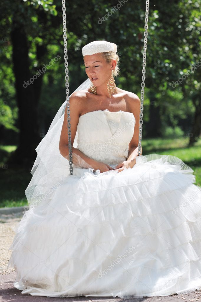 Beautiful bride woman in fashion wedding dress posing outdoor in bright park at morning — Stock fotografie #6852348