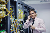 It engeneer talking by phone at network room — Stockfoto