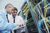Lo ingenieros en sala de servidores de red — Foto de Stock