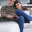 Relaxed young couple watching tv at home — Stock Photo #7400170