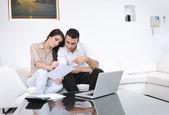 Glada par koppla av och arbeta på bärbar dator i moderna hem — Stockfoto