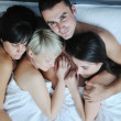 Young handsome man lying in bed with three girls — Stock Photo