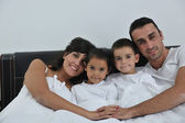 Happy young Family in their bedroom — Stock Photo