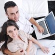 Joyful couple relax and work on laptop computer at modern home — Стоковая фотография
