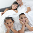 Happy young Family in their bedroom - Stockfoto