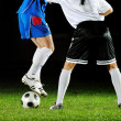 Football players in action for the ball - Stock Photo