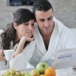 Happy couple reading the newspaper in the kitchen at breakfast - Stock Photo