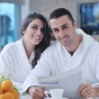Happy couple reading the newspaper in the kitchen at breakfast - Stock fotografie
