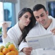 Happy couple reading the newspaper in the kitchen at breakfast — Foto Stock