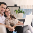 Joyful couple relax and work on laptop computer at modern home - Stock Photo