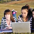 Group of teens working on laptop outdoor — Stockfoto #7830629
