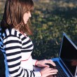 Young girl work on laptop outdoor — Stock Photo