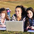 Foto Stock: Group of teens working on laptop outdoor