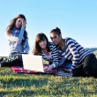 Group of teens working on laptop outdoor — Stockfoto