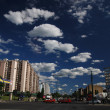 Traffic in the city and blue sky with dramatic clouds — Stok fotoğraf