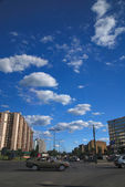 Traffic in the city and blue sky with dramatic clouds — Stock Photo