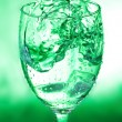 Glass with splash on green background — Stock Photo