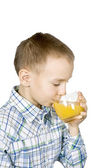 Boy drinking orange juice. — Stock Photo