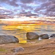 Stones in sunset ocean — Stock Photo
