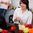Stock Photo: Young woman in the kitchen preparing salad