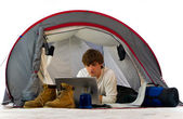 Man working with laptop in tent — Stock Photo