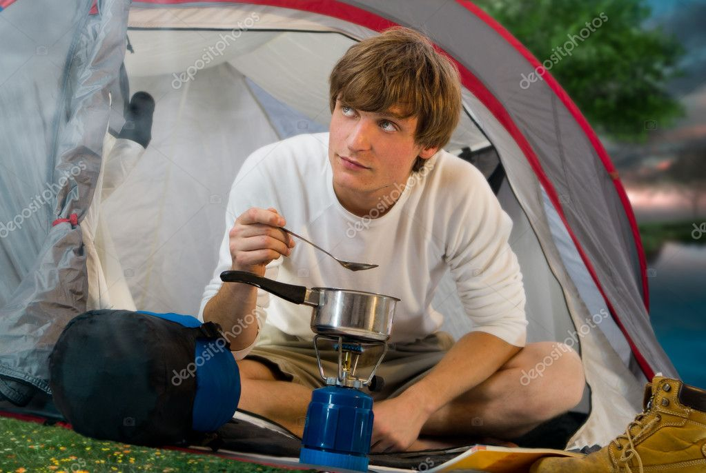Young man at tent outdoor and cooking — Stock Photo #6838068