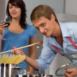 Happy young couple in the kitchen cooking dinner — Stock Photo
