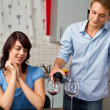 Young smiling couple drink red wine in modern kitchen — ストック写真