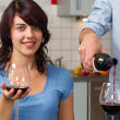 Young smiling couple drink red wine in modern kitchen — Stock Photo
