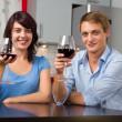 genç gülümseyen bir çift kırmızı şarap içmek modern bir mutfak — Stok fotoğraf