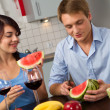 Young couple drink red wine and eat watermelon — Stock Photo