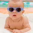 Funny baby in sunglasses on the beach — Stock Photo