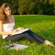 Young woman painting on a green meadow — Stock Photo