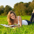 Young woman reeding on a green meadow — Stock Photo #7605264
