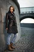 Beautiful young woman near stone wall — Stock Photo