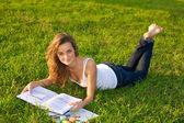 Beautiful уoung woman reeding on a green meadow — Stok fotoğraf