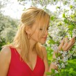 Young woman in red dress enjoying smell of blooming tree — Stock Photo