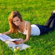 Beautiful young woman reeding on a green meadow — Stock Photo