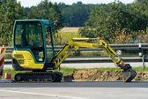 Mini excavator on motorway — Stock Photo